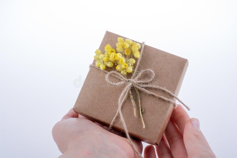 Contenitore di regalo con i fiori a disposizione fotografie stock libere da diritti