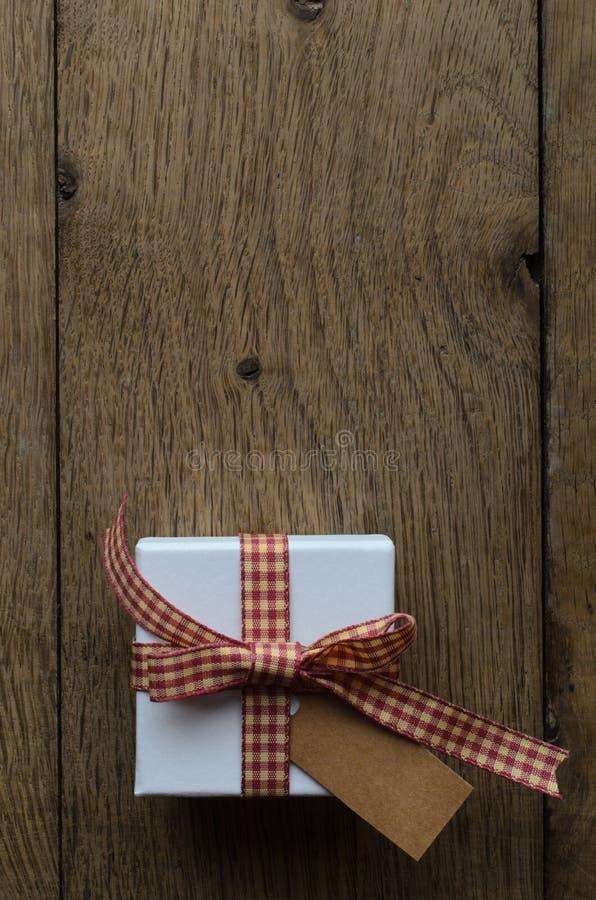 Contenitore di regalo con il nastro del percalle ed etichetta in bianco su legno immagine stock