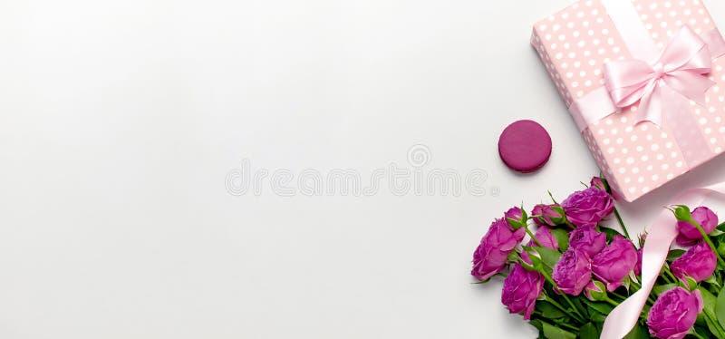 Contenitore di regalo con il nastro, le rose rosa luminose, il macaron del dolce o il maccherone su fondo grigio chiaro Disposizi immagine stock libera da diritti