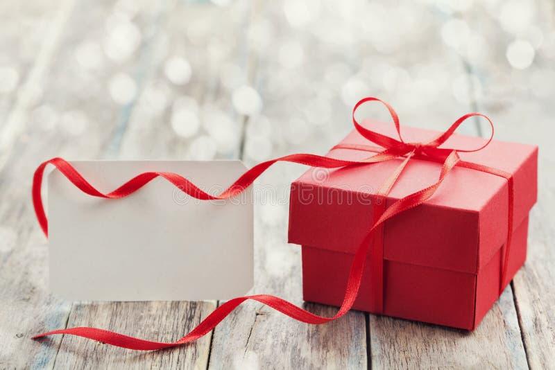 Contenitore di regalo con il nastro rosso dell'arco e nota di carta vuota sulla tavola per il giorno di biglietti di S. Valentino immagini stock