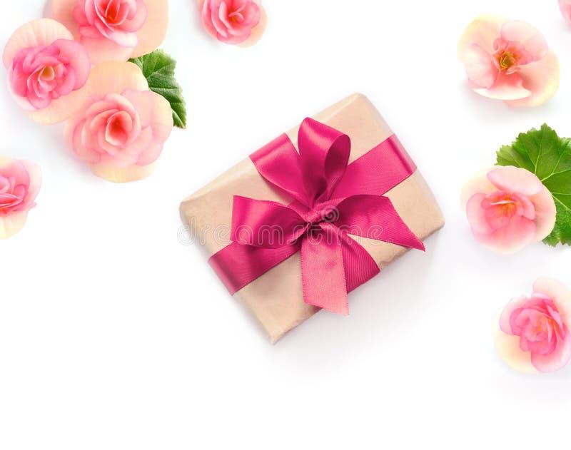 Contenitore di regalo con il nastro rosso ed arco su bianco con il fondo dei fiori lat piano, vista superiore fotografie stock libere da diritti