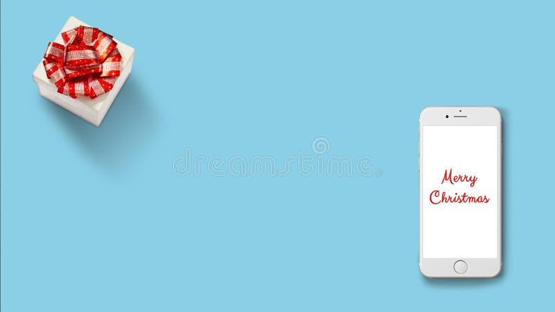 Contenitore di regalo con il nastro rosso su Libro Bianco su fondo rosso con Smartphone immagine stock