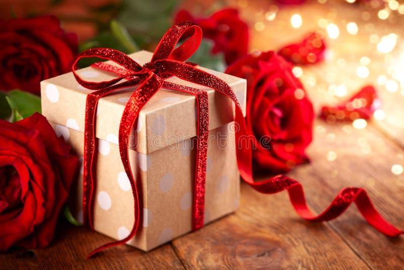 Contenitore di regalo con l'arco rosso del nastro e rose rosse per la festa immagine stock