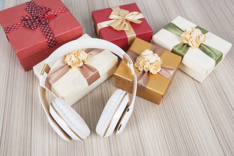 Contenitore di regalo con le cuffie sulla tavola di legno immagine stock