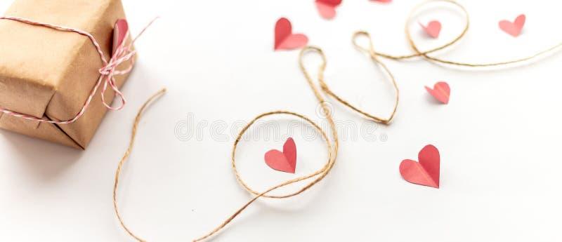 Contenitore di regalo d'annata di giorno di biglietti di S. Valentino su fondo bianco con l'arco di carta rosa, corda della iuta, immagine stock