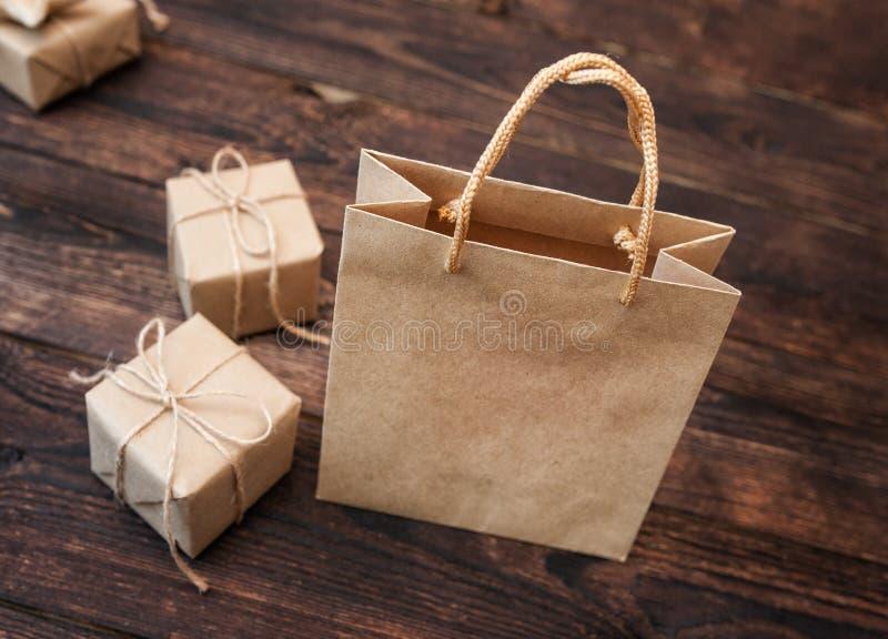 Contenitore di regalo del cartone di Kraft del modello e pacchetto della maniglia su fondo di legno per progettazione, sito Web,  immagine stock