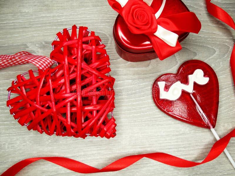 Contenitore di regalo del cuore di giorno del ` s del biglietto di S. Valentino e lecca-lecca dolce immagine stock