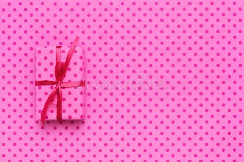Contenitore di regalo della festa su carta da imballaggio rosa con i pois fotografia stock