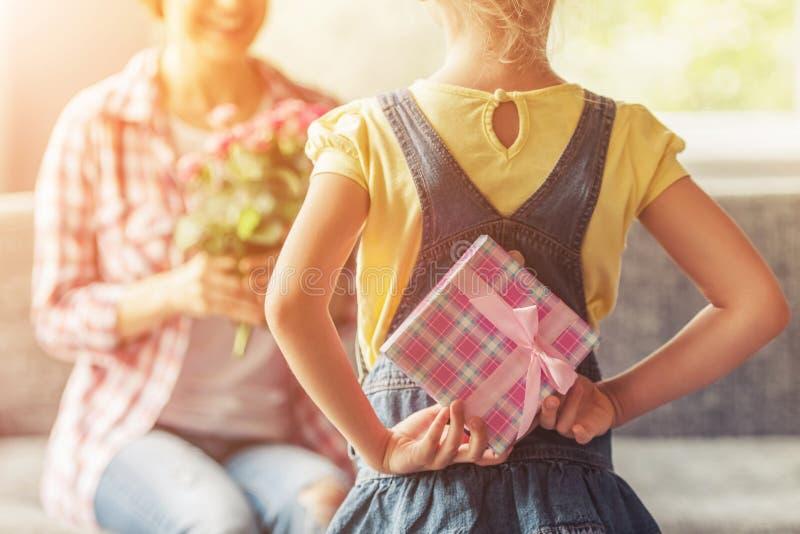 Contenitore di regalo della tenuta della bambina per la sua bella mamma immagini stock