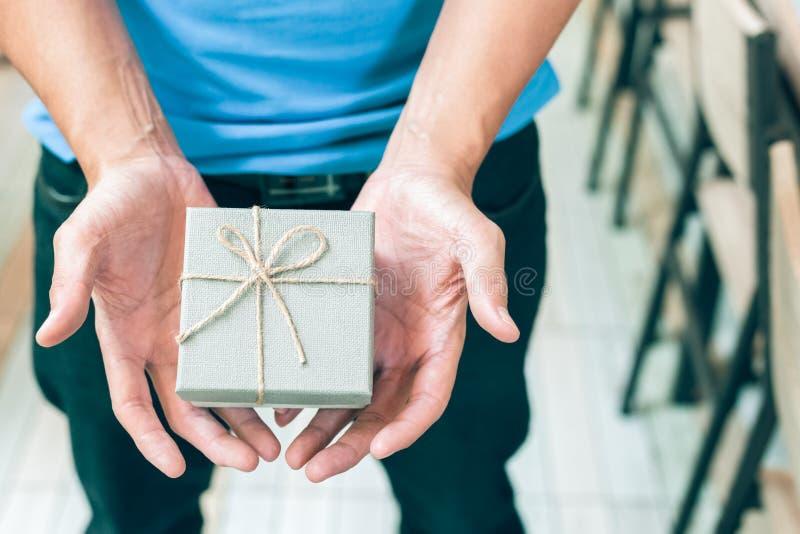Contenitore di regalo della tenuta della mano del ` s degli uomini immagine stock