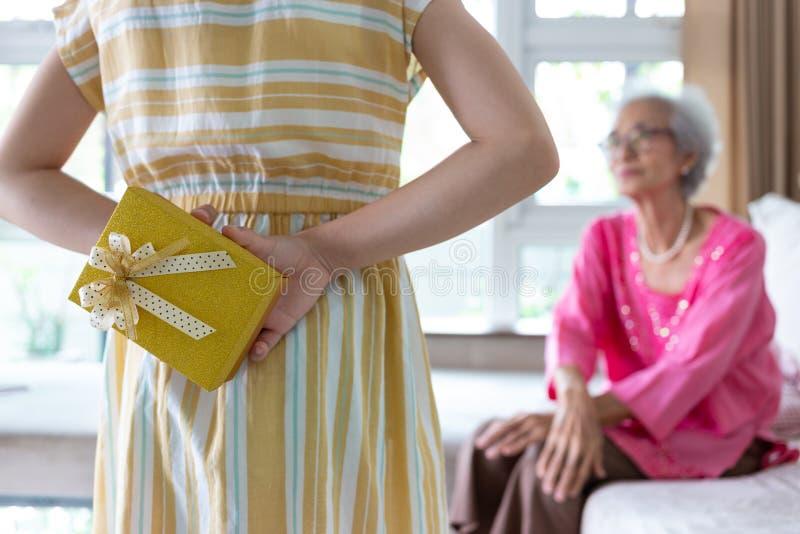 Contenitore di regalo della tenuta della nipote per la loro bella nonna dietro fotografie stock