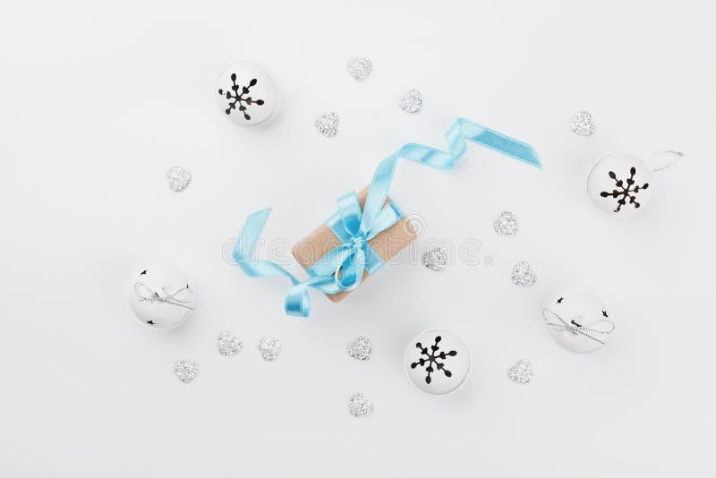 Contenitore di regalo di Natale con il nastro blu e campana di tintinnio sulla tavola bianca da sopra Cartolina d'auguri di festa fotografia stock libera da diritti