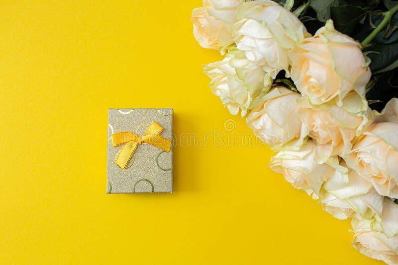 Contenitore di regalo e rose bianche su fondo giallo da sopra, struttura posta piana fotografie stock