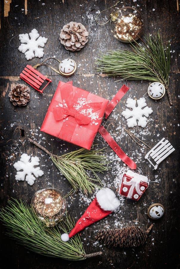 Contenitore di regalo festivo di Natale rosso con le decorazioni di festa e di inverno su fondo di legno rustico immagini stock