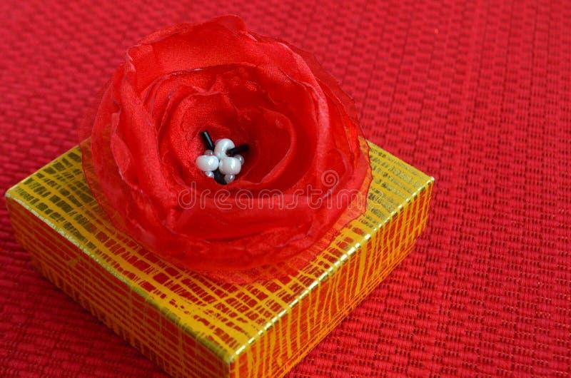 Contenitore di regalo giallo con la fine rossa della decorazione del fiore del tessuto su fotografia stock libera da diritti