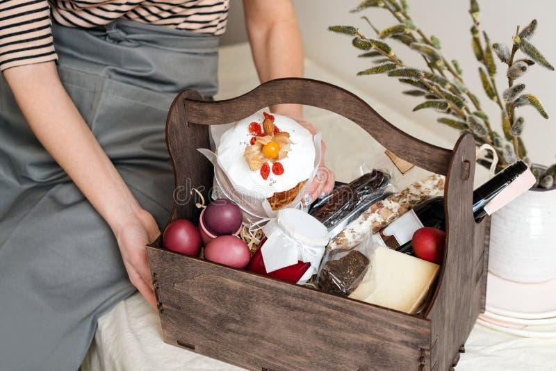 Contenitore di regalo di legno in mani femminili con i fiori della molla sul fondo leggero del tessuto naturale Canestro di Pasqu immagini stock