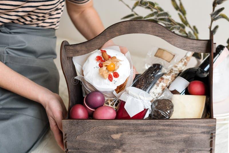 Contenitore di regalo di legno in mani femminili con i fiori della molla sul fondo leggero del tessuto naturale Canestro di Pasqu fotografia stock libera da diritti