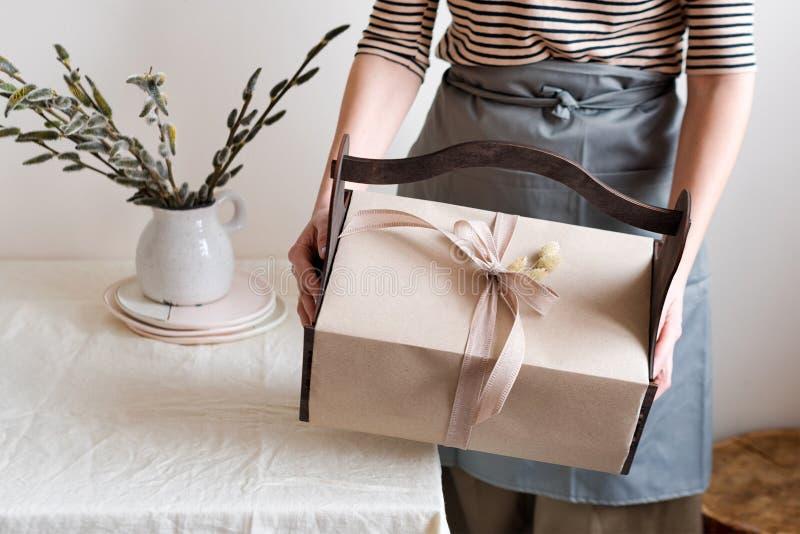 Contenitore di regalo in mani femminili con i fiori della molla sul fondo leggero del tessuto naturale Canestro di Pasqua con i p immagine stock