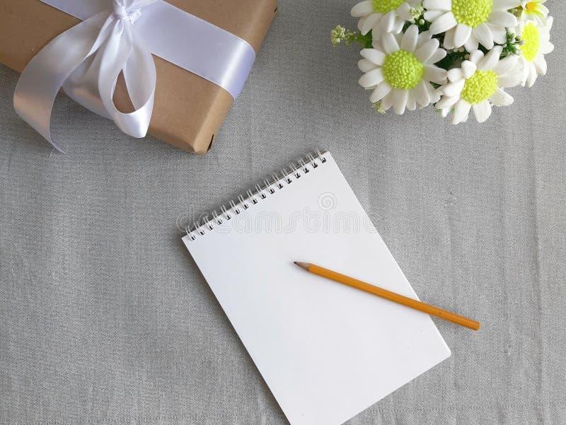 Contenitore di regalo, mazzo dei fiori, blocco note di carta in bianco con la matita su fondo grigio immagine stock libera da diritti