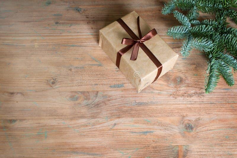 Contenitore di regalo di natale ed albero di abete semplici su fondo di legno vuoto fotografie stock