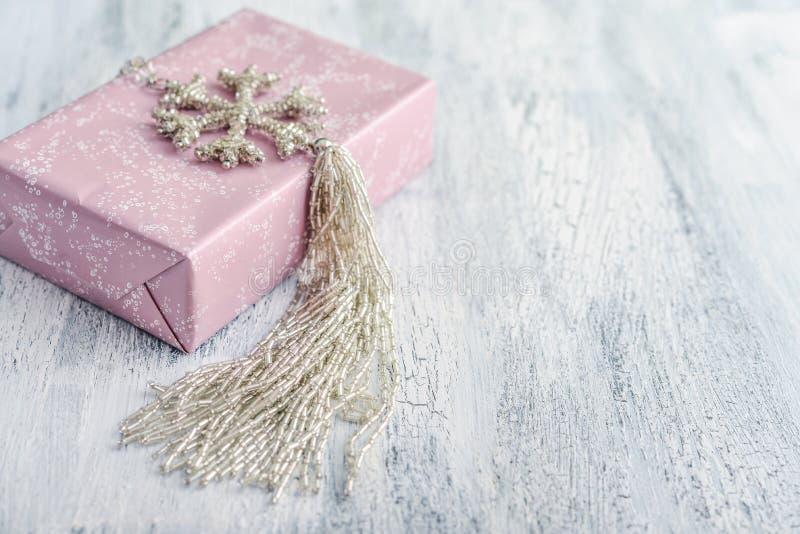 Contenitore di regalo rosa con la decorazione di natale nella forma del fiocco di neve fotografia stock libera da diritti