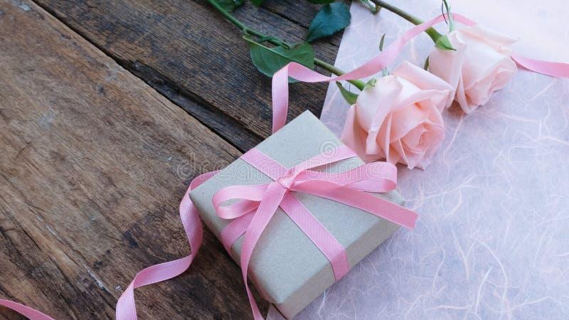 Contenitore di regalo rosa del nastro e rosa arancio-rosa sulla tavola di legno d'annata per Valentine& x27; concetto di s immagine stock