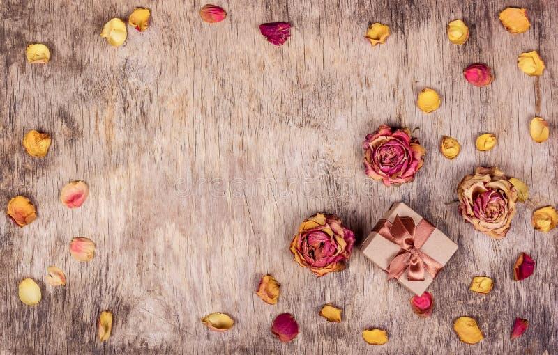 Contenitore di regalo, rose asciutte e fondo di legno Fiori asciutti, rose secche fotografie stock libere da diritti