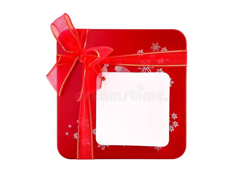 Contenitore di regalo rosso con il nastro e l'etichetta in bianco della nota isolati immagini stock