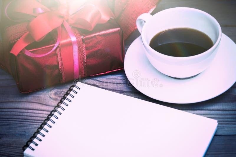 Contenitore di regalo rosso con il nastro su un fondo di legno Una tazza di caffè fotografie stock
