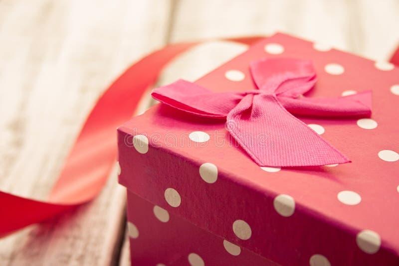 Contenitore di regalo rosso con il nastro sulla tavola di legno bianca rustica valentine fotografia stock