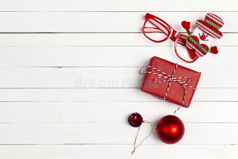 Contenitore di regalo rosso con le decorazioni di Natale su fondo di legno bianco Vista superiore, disposizione piana fotografia stock