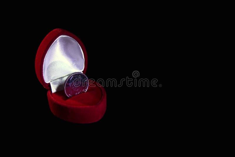 Contenitore di regalo rosso del velluto con una moneta invece di un anello su fondo nero isolato che simbolizza un matrimonio di  fotografia stock