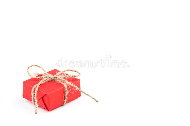 Contenitore di regalo rosso della carta del mestiere legato con l'isolato marrone del nastro dell'arco della corda fotografia stock