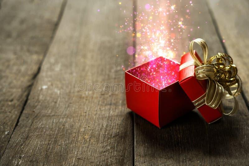 Contenitore di regalo rosso di Natale con le luci magiche variopinte sullo scrittorio di legno fotografie stock