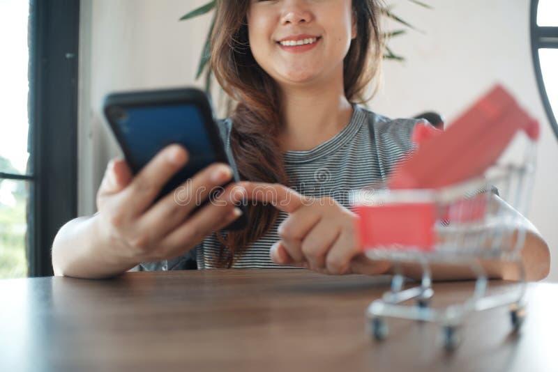 Contenitore di regalo rosso sul carrello con le donne che per mezzo del telefono cellulare immagini stock