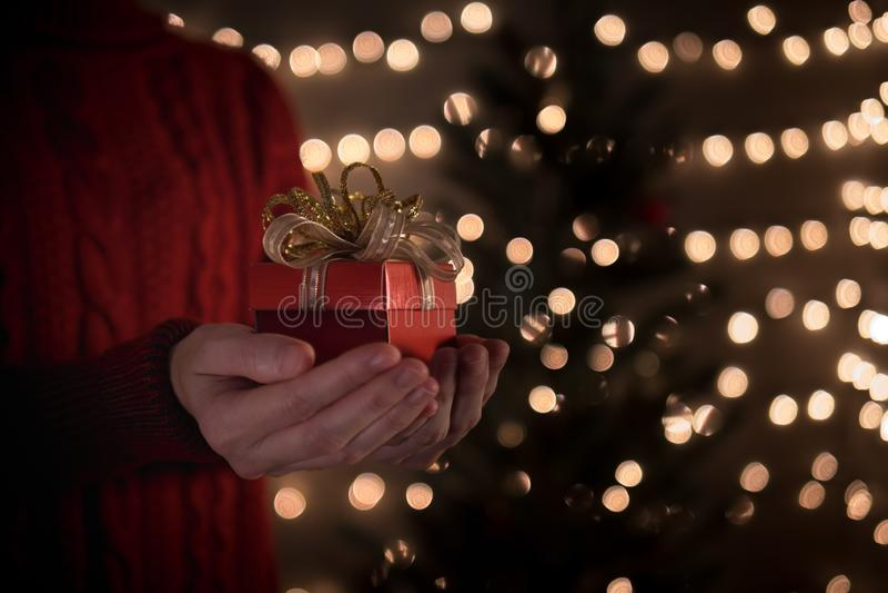 Contenitore di regalo rosso di tenuta femminile di Natale sul fondo delle luci del bokeh fotografia stock