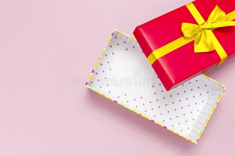 Contenitore di regalo rosso vuoto aperto con il nastro dell'oro sulla disposizione piana rosa-chiaro di vista superiore del fondo fotografia stock