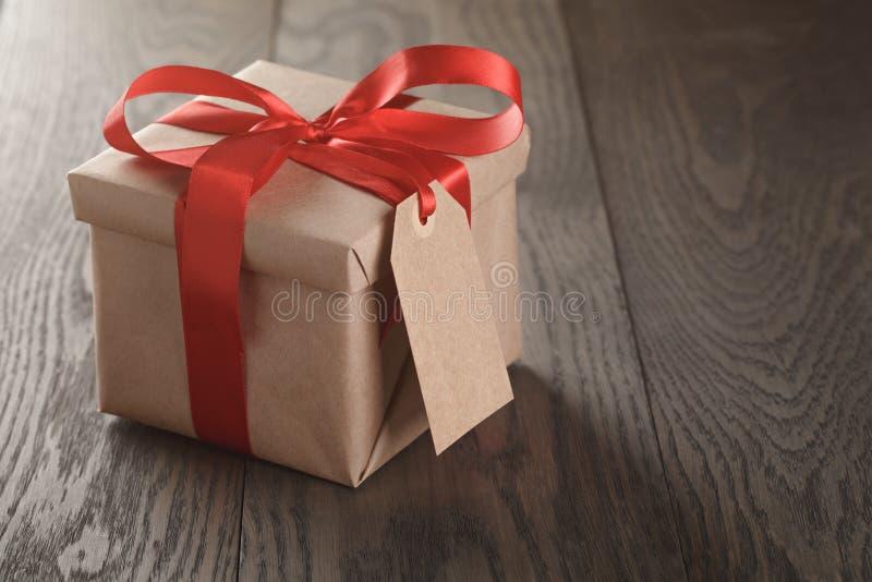 Contenitore di regalo rustico con l'arco rosso del nastro e l'etichetta emmpty fotografia stock