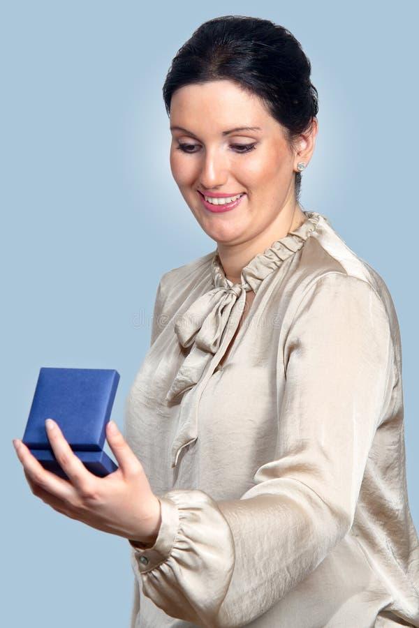 Contenitore di regalo sorpreso della tenuta della donna in mani fotografia stock