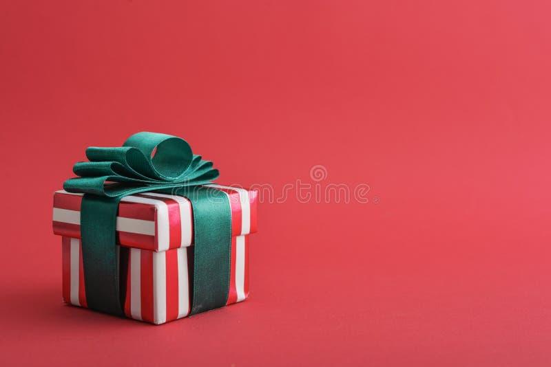 Contenitore di regalo a strisce rosso con il nastro verde fotografia stock