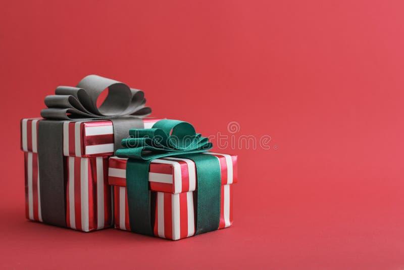 Contenitore di regalo a strisce rosso due con il nastro verde e grigio fotografia stock libera da diritti