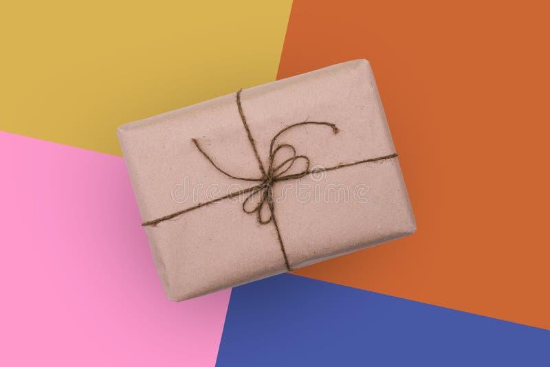 Contenitore di regalo su un fondo colorato La scatola è avvolta in carta del cartone ed è legata con un filo spesso Un regalo per immagini stock libere da diritti