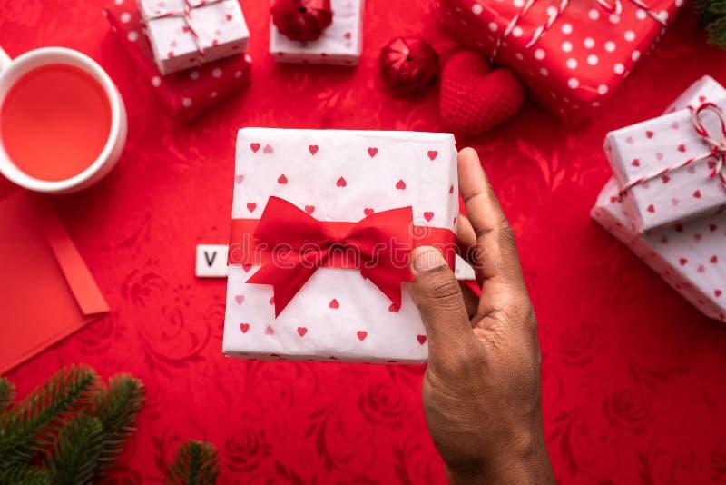 Contenitore di regalo umano della tenuta della mano sul fondo rosso della tovaglia Fondo di celebrazione di San Valentino fotografie stock