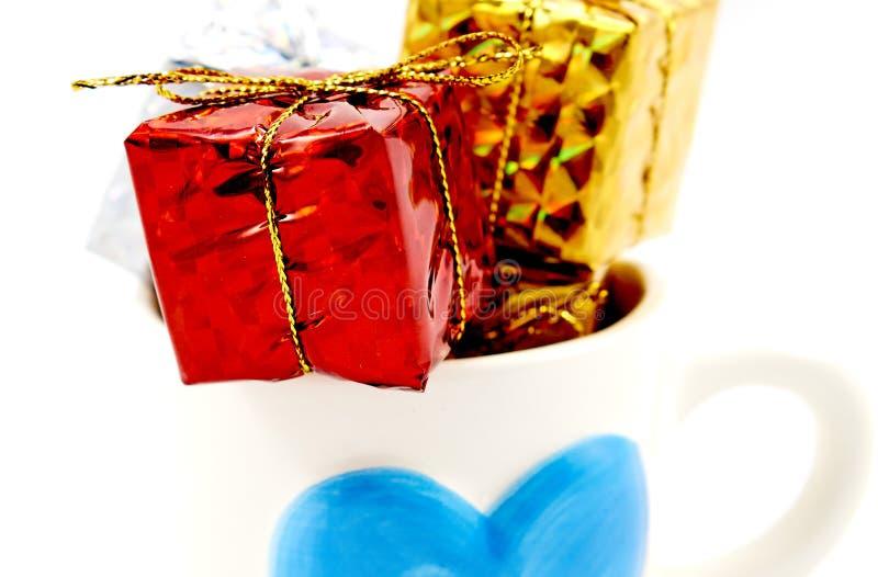 Contenitore di regalo in una tazza immagine stock libera da diritti