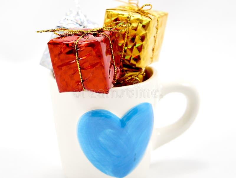 Contenitore di regalo in una tazza immagini stock