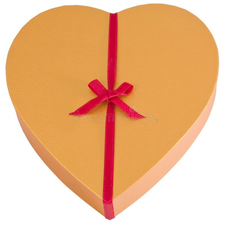 Contenitore dorato a forma di di cioccolato del cuore con il nastro fotografia stock libera da diritti