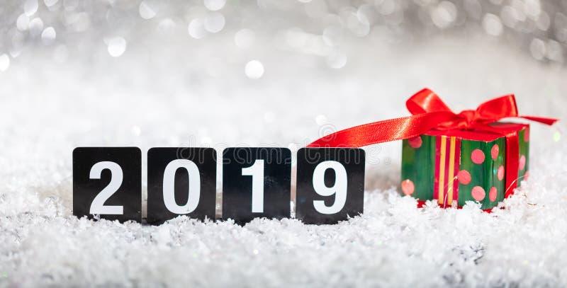 Contenitore e nuovo anno di regalo di Natale 2019, su neve, fondo astratto delle luci del bokeh immagini stock