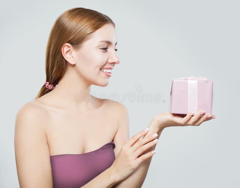 Contenitore e sorridere di regalo felice di rappresentazione della giovane donna immagini stock