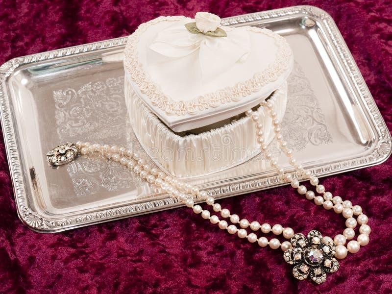 Contenitore Heart-shaped di raso con le perle sul cassetto d'argento fotografie stock libere da diritti