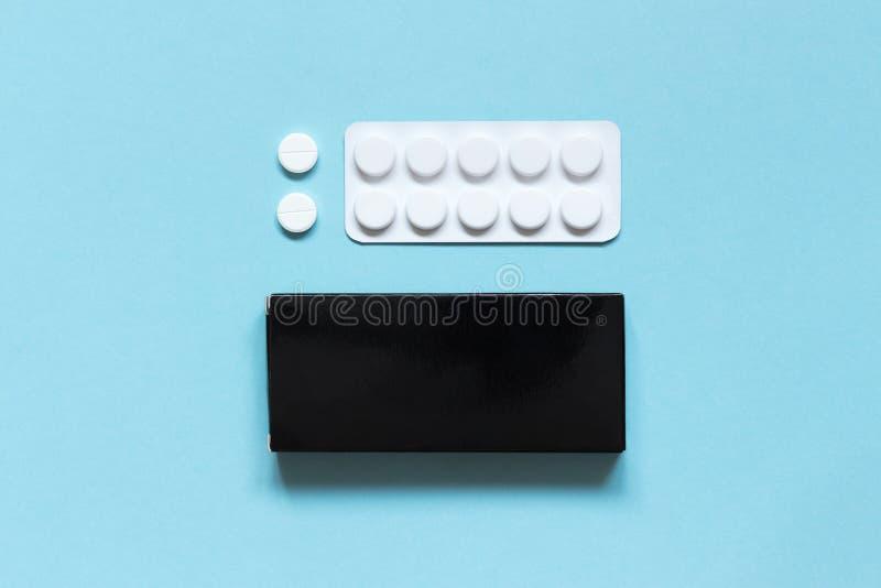 Contenitore nero di cartone, bolla e pillole bianche su un fondo blu farmaci fotografie stock